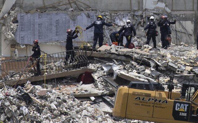 Des membres de l'équipe de recherche et de sauvetage urbain du sud de la Floride cherchent d'éventuels survivants dans l'immeuble résidentiel Champlain Towers South de 12 étages partiellement effondré, le 26 juin 2021 à Surfside, en Floride. (Crédit : JOE RAEDLE / GETTY IMAGES NORTH AMERICA / Getty Images via AFP)