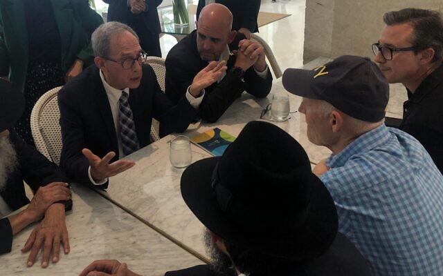 Nachman Shai, deuxième à gauche, parle au sénateur Rick Scott, en casquette, au Grand Beach Hotel de Surfside, en Floride, le 27 juin 2021. (Crédit : Ron Kampeas)