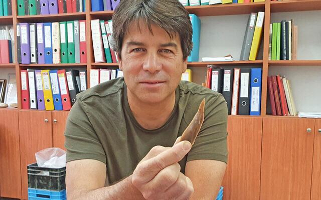 Le Dr Omry Barzilai, préhistorien, avec un outil en silex provenant de Boker Tachtit, vieux de 50 000 ans. (Crédit : Autorité israélienne des antiquités)