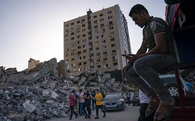 Des personnes se rassemblent pour voir les décombres de l'immeuble al-Jalaa dans la ville de Gaza, vendredi 21 mai 2021. L'immeuble a abrité le bureau de l'Associated Press dans la ville de Gaza pendant 15 ans. (Crédit : AP/John Minchillo)