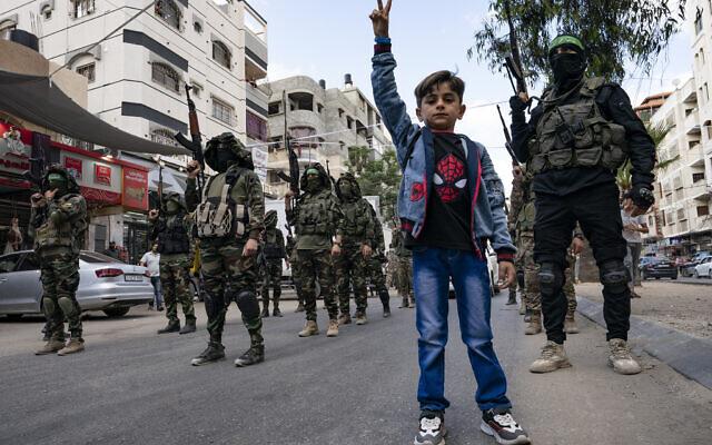Des enfants devant les militants du Hamas lors d'un défilé en hommage à Bassem Issa, commandant du groupe terroriste qui a été tué par l'armée israélienne avant le cessez-le-feu qui a mis un terme au conflit de onze jours entre Israël et les groupes terroristes de la bande de Gaza, le 22 mai 2021. (Crédit : AP Photo/John Minchillo)