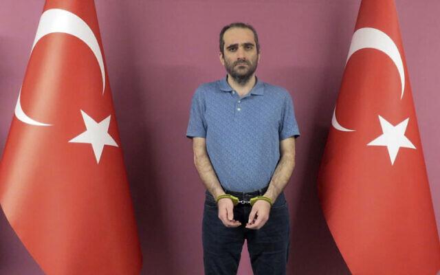 Selahattin Gulen, un neveu du religieux musulman Fethullah Gulen basé aux États-Unis, se tient entre des drapeaux turcs sur cette photo fournie par les services de renseignement turcs, le lundi 31 mai 2021, à Ankara, en Turquie.  (Crédit : Service de renseignement turc via AP)