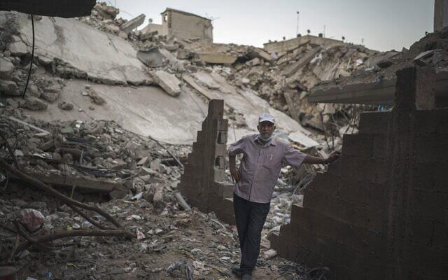 Un homme devant sa maison lourdement endommagée, à côté des décombres d'un bâtiment qui a été touché par des frappes aériennes lors de la guerre de 11 jours entre les dirigeants du Hamas de Gaza et Israël, dans la ville de Gaza, mardi 1er juin 2021. (Crédit : AP Photo/Felipe Dana)