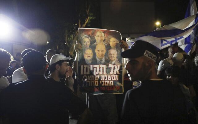 La police israélienne lors d'une manifestation de droite dénonçant le gouvernement d'unité avec un panneau montrant Naftali Bennett et d'autres membres du parti Yamina ainsi que le politicien Ahmad Tibi, à droite, et Mansour Abbas, à gauche, à Ramat Gan, dans le centre d'Israël, le 2 juin 2021. (Crédit : AP Photo/Sebastian Scheiner)