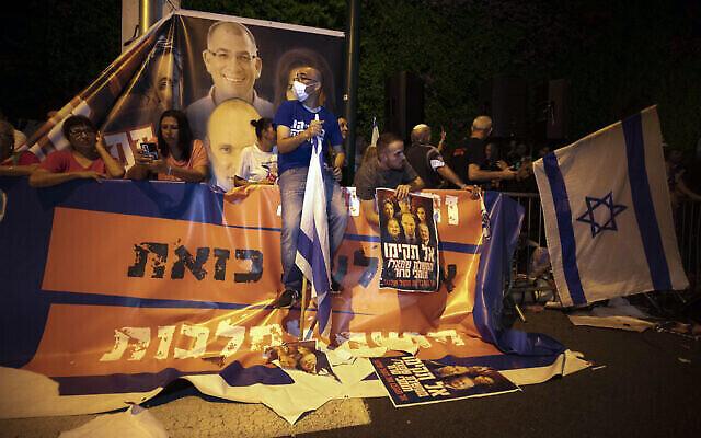 Des manifestants israéliens de droite scandent des slogans et brandissent des drapeaux lors d'une manifestation contre la formation d'un nouveau gouvernement dans la ville centrale d'Israël de Ramat Gan, le mercredi 2 juin 2021. (Crédit: AP/Sebastian Scheiner)
