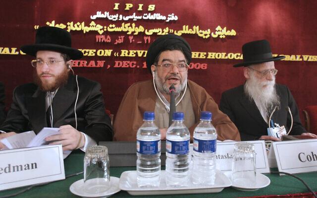 Le dignitaire religieux Ali Akbar Mohtashamipour, au centre, parle lors d'une conférence sur le négationnisme avec le rabbin Moishe Arye Friedman, à gauche, d'Autriche, et le rabbin Ahron Cohen, à droite, d'Angleterre, à Téhéran, en Iran, le 11 décembre 2006. (Crédit : AP/Vahid Salemi)
