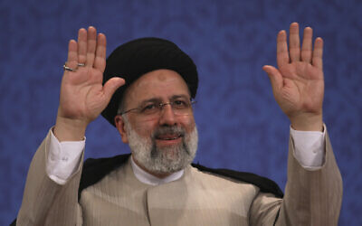 Le nouveau président iranien Ebrahim Raissi  salue les journalistes à la fin d'une conférence de presse à Téhéran, le 21 juin 2021. (Crédit :Vahid Salemi/AP)