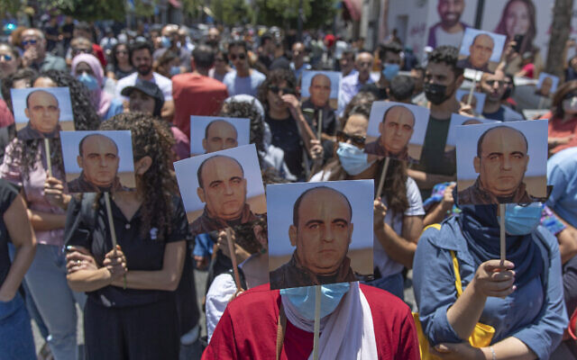 Des manifestants en colère portent des photos de Nizar Banat, un critique virulent de l'Autorité palestinienne, et scandent des slogans contre l'Autorité palestinienne lors d'un rassemblement pour protester contre sa mort, dans la ville de Ramallah, en Cisjordanie, le 24 juin 2021. (Crédit : AP Photo/Nasser Nasser)