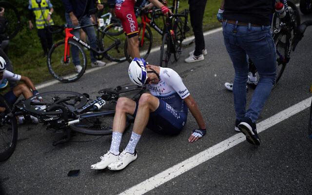 Chris Froome est allongé sur la route après avoir chuté lors de la première étape du Tour de France, le 26 juin 2021. (Crédit : AP Photo/Daniel Cole)