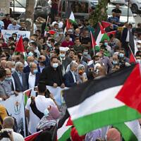 Des Palestiniens agitent des drapeaux nationaux lors d'une manifestation contre la normalisation des liens entre les Emirats arabes unis et le Bahreïn avec Israël, dans la ville de Ramallah, en Cisjordanie, le 15 septembre 2020. (Crédit : Majdi Mohammed/AP)