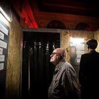 """Des spectateurs lisent des documents dans l'une des 11 stations de """"Macho Man"""", une installation audiovisuelle sur la violence domestique, dans le cadre du Festival d'Israël, en juin 2021. (Crédit : Marti Artalejo)"""