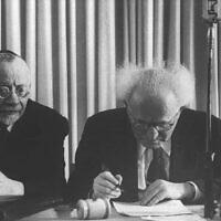David Ben Gurion signe la déclaration d'indépendance israélienne, le 29 novembre 1947. (Crédit : Hans Pinn/GPO)