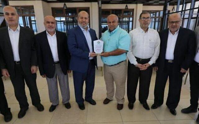 """Des responsables du Hamas remettent un certificat à Al Jazeera après ce que le groupe terroriste a décrit comme un """"haut niveau de nationalisme"""" de la part du média dans sa couverture du conflit du mois dernier avec Israël, le 10 juin 2021. (Crédit : via Twitter)"""