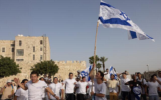 De jeunes Juifs dansent avec des drapeaux israéliens aux abords de la Vieille Ville de Jérusalem, le 10 mai 2021. (Crédit : Nati Shohat/Flash90)