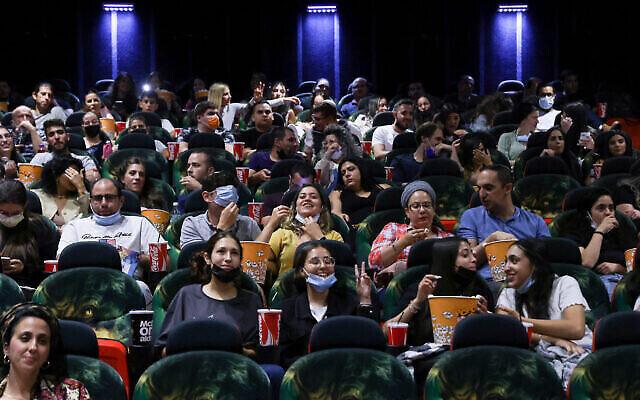 Des Israéliens assistent à un film au cinéma Cinema City lors de la soirée de réouverture officielle après 14 mois de fermeture pendant la pandémie de coronavirus, le 27 mai 2021 à Jérusalem. (Crédit : Olivier Fitoussi/Flash90)