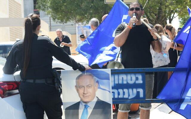 Un homme utilise un haut-parleur lors d'une manifestation organisée devant l'habitation du leader du parti Yamina,  Naftali Bennet, lors des négociations visant à former un gouvernement à Raanana, le 4 juin 2021. (Crédit : Avshalom Sassoni/Flash90)