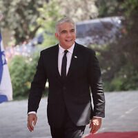Le nouveau ministre des Affaires étrangères Yair Lapid arrive à une séance de photo de groupe du tout nouveau gouvernement à la résidence du président de Jérusalem, le 14 juin 2021. (Crédit :  Yonatan Sindel/FLASH90)