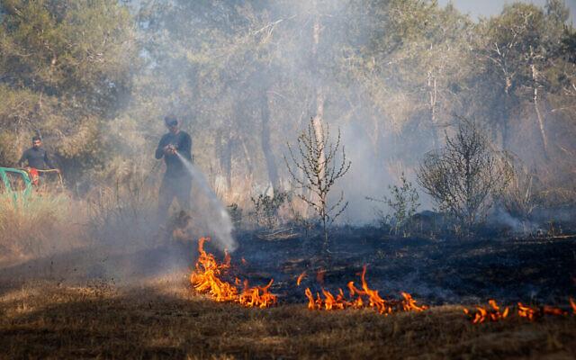 Dans le sud d'Israël, les pompiers tentent d'éteindre un incendie déclenché par un engin incendiaire héliporté lancé par des Palestiniens depuis la bande de Gaza, le 15 juin 2021. (Flash90)