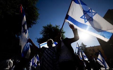 Des hommes juifs dansent avec des drapeaux israéliens lors de la marche annuelle des Drapeaux près de la Vieille Ville de Jérusalem, le 15 juin 2021. (Crédit : Yonatan Sindel/Flash90)
