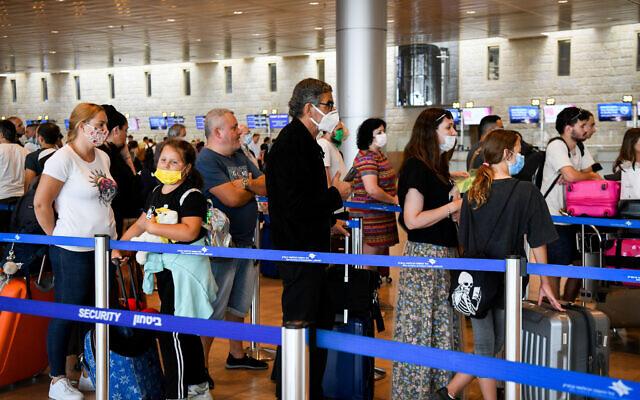 Des voyageurs masqués rassemblés  à l'aéroport Ben-Gurion, dans le hall des départs, le 23 juin 2021. (Crédit : Flash90)