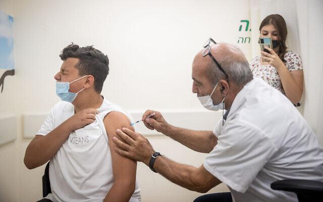 Un jeune Israélien se fait vacciner à la COVID-19 dans un centre de vaccination de la Clalit à Jérusalem, le 24 juin 2021. (Crédit : Yonatan Sindel/Flash90)