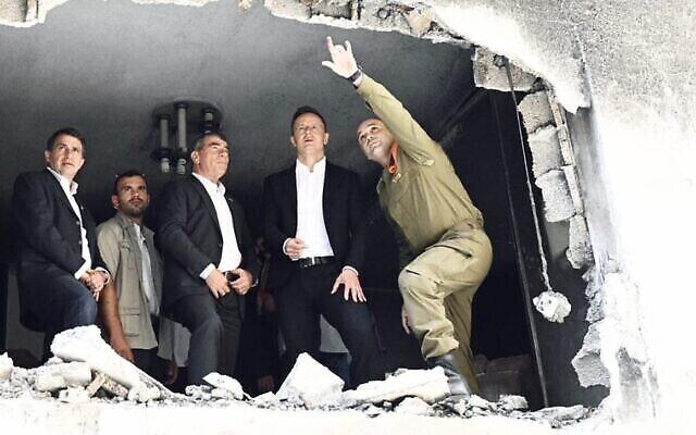"""Le ministre des Affaires Etrangères, Gabi Ashkenazi et son homologue hongrois, Peter Szijjartoon, visitent une maison dans la ville centrale de Petah Tikva qui a été touchée par une roquette tirée par des terroristes palestiniens à Gaza pendant l'opération de Tsahal """"Gardien des murs"""", le 1er juin 2021. (Crédit : Courtoisie)"""