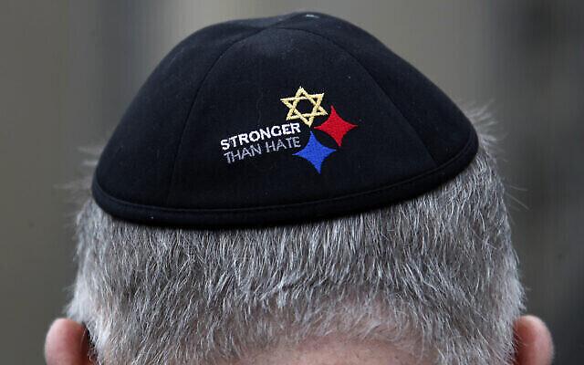 Un homme portant un Yamulke (= Kippa) Stronger Than Hate se tient devant la synagogue Tree of Life à Pittsburgh, le dimanche 27 octobre 2019, premier anniversaire de la fusillade à la synagogue, qui a tué 11 fidèles.(Crédit:AP Photo/Gene J. Puskar).