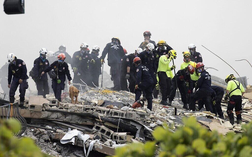 Des membres de l'équipe de recherche et de sauvetage urbain de Floride du Sud recherchent d'éventuels survivants dans l'immeuble à condos Champlain Towers South de 12 étages partiellement effondré, le 25 juin 2021 à Surfside, en Floride. (Crédits:Joe Raedle/Getty Images)