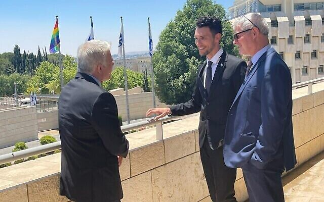 Le ministre des Affaires étrangères Yair Lapid, le vice-ministre des Affaires étrangères Idan Roll et le directeur général du ministère des Affaires étrangères Alon Ushpiz, à côté du drapeau LGBT installé le 21 juin 2021. (Crédit : Ministère des affaires étrangères)