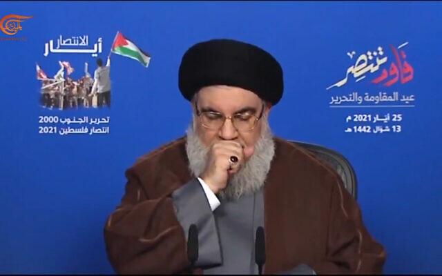 Le chef du Hezbollah, Hasan Nasrallah, tousse lors d'une allocution le 25 mai 2021 (Crédit : capture d'écran Twitter)