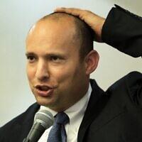Naftali Bennett, en 2014, prononce un discours en tenant sa kippa sur la tête. (Menahem Kahana/AFP)