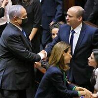 Le Premier ministre sortant d'Israël, Benjamin Netanyahu, serre la main de son successeur, le Premier ministre entrant Naftali Bennett, après une session spéciale pour voter sur un nouveau gouvernement à la Knesset à Jérusalem, le 13 juin 2021. (Emmanuel Dunand / AFP)
