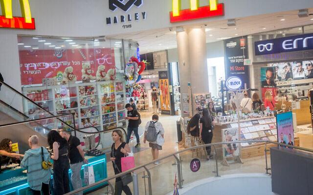 Des personnes font du shopping au centre commercial Dizengoff Center à Tel Aviv le 14 juin 2021, après que le ministère de la Santé a annoncé la fin de l'obligation de porter un masque dans les lieux publics fermés (COVID-19). (Miriam Alster/Flash90)