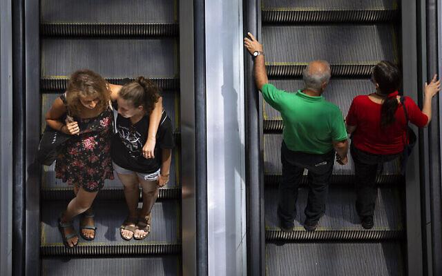Des personnes empruntent un escalator dans un centre commercial après la levée des restrictions imposant le port de masques à l'intérieur, à Tel Aviv, le mardi 15 juin 2021. (AP Photo/Oded Balilty)