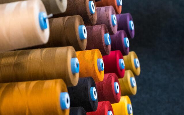 Bobines de fil coloré utilisées dans l'industrie du textile et de la confection (Crédit : Ja'Crispy ; iStock by Getty Images)