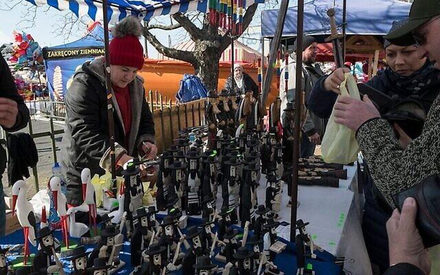 Les clients d'un marché de Cracovie achètent des figurines d'hommes orthodoxes hassidiques. (Crédit : Jason Francisco via JTA)