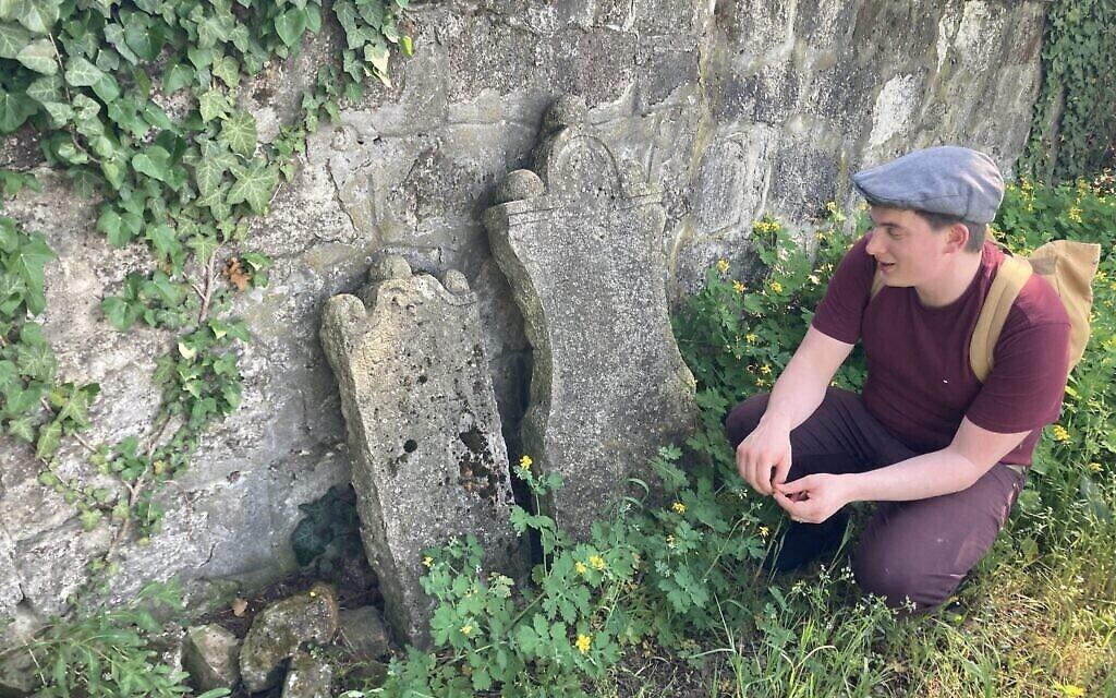 Matyas Kiraly s'agenouille à côté de certaines des pierres tombales les plus anciennes, datant de 1750, dans l'ancien cimetière juif de Nagyteteny, le 11 mai 2021. (Crédit : Yaakov Schwartz/ Times of Israel)