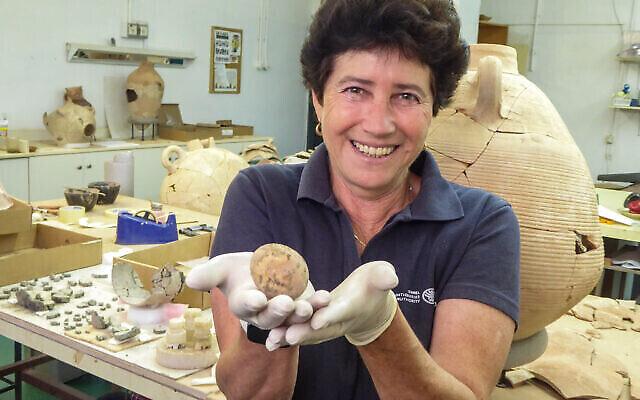 Alla Nagorsky, archéologue de l'Autorité israélienne des antiquités, avec l'œuf vieux de 1000 ans qui a été retrouvé à Yavne. (Crédit : Yoli Schwartz/Israel Antiquities Authority)
