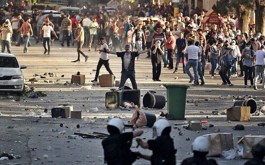 Un homme se tient debout, la poitrine dénudée, lors d'affrontements entre des manifestants palestiniens et les forces de sécurité palestiniennes dans la ville de Ramallah, en Cisjordanie, le 26 juin 2021, à la suite d'une manifestation contre la mort du militant des droits de l'homme Nizar Banat, alors qu'il était détenu par les forces de sécurité de l'Autorité palestinienne (AP) en début de semaine. (ABBAS MOMANI / AFP)