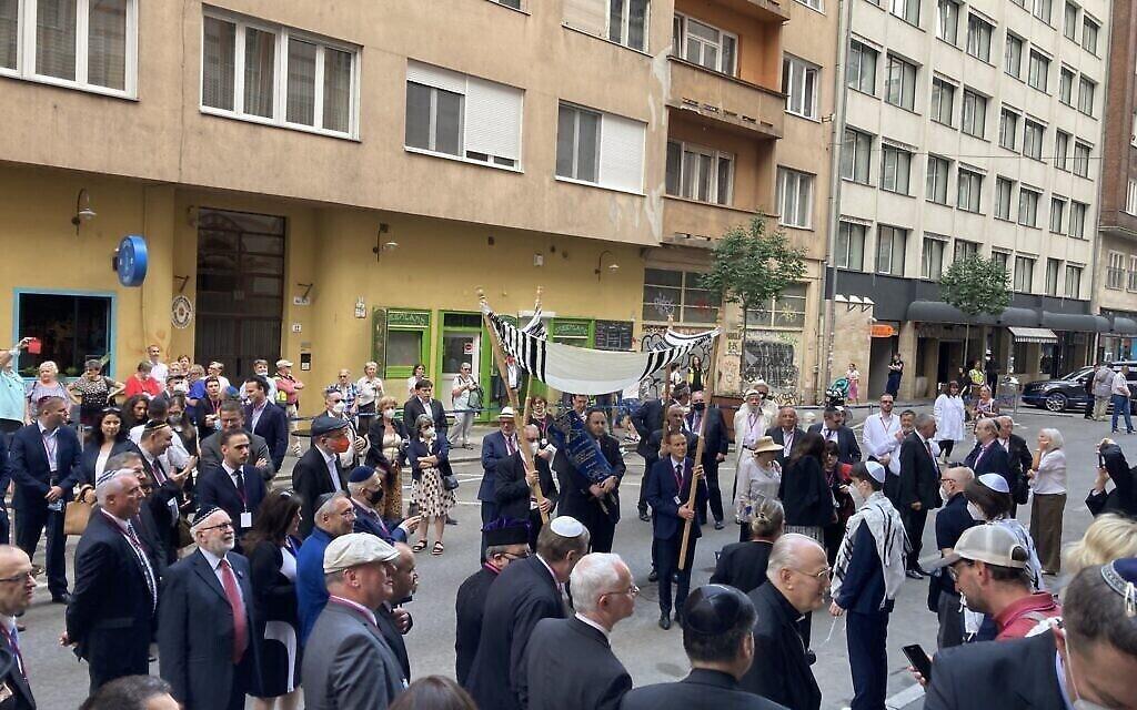 Des membres de la communauté juive de Budapest dansent avec la Torah devant la synagogue Rumbach, le 10 juin 2021. (Yaakov Schwartz/ Times of Israel)