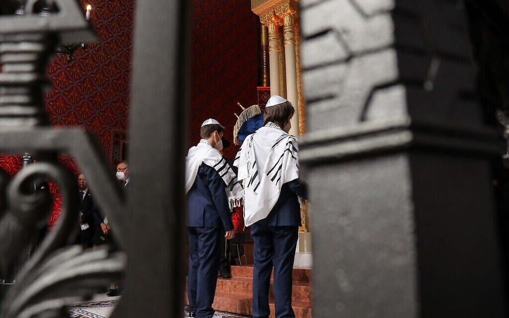 Deux garçons bar-mitsvah aident à placer la Torah dans l'arche lors de la cérémonie de réouverture de la synagogue Rumbach, le 10 juin 2021. (Photo d'Akos Szentgyorgyi)