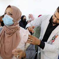Fichier : Des Palestiniens reçoivent le vaccin COVID-19 de Pfizer-BioNTech dans la ville de Hébron, en Cisjordanie, le 27 mars 2021 (Wisam Hashlamoun/Flash90).