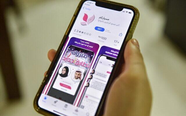 """Une femme avec un smartphone à la main montrant une application de mariage """"Misyar"""" en Arabie saoudite, le 29 octobre 2020. (Crédit :  FAYEZ NURELDINE / AFP)"""