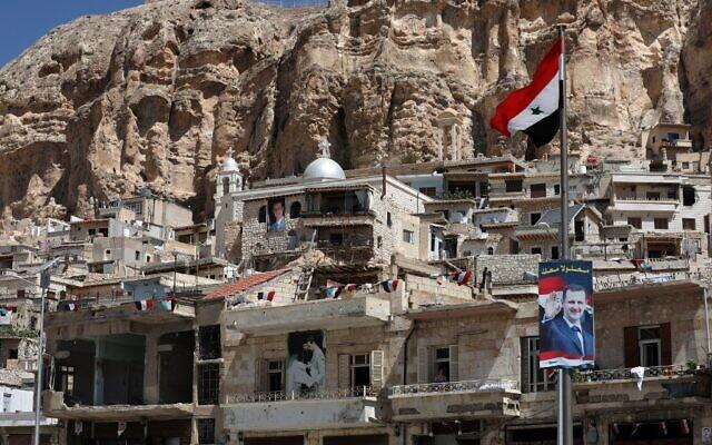 Un drapeau national et des portraits du président syrien Bashar al-Assad dans le village de Maalula, au nord Damas, le 29 juin 2021. (Crédit : LOUAI BESHARA / AFP)