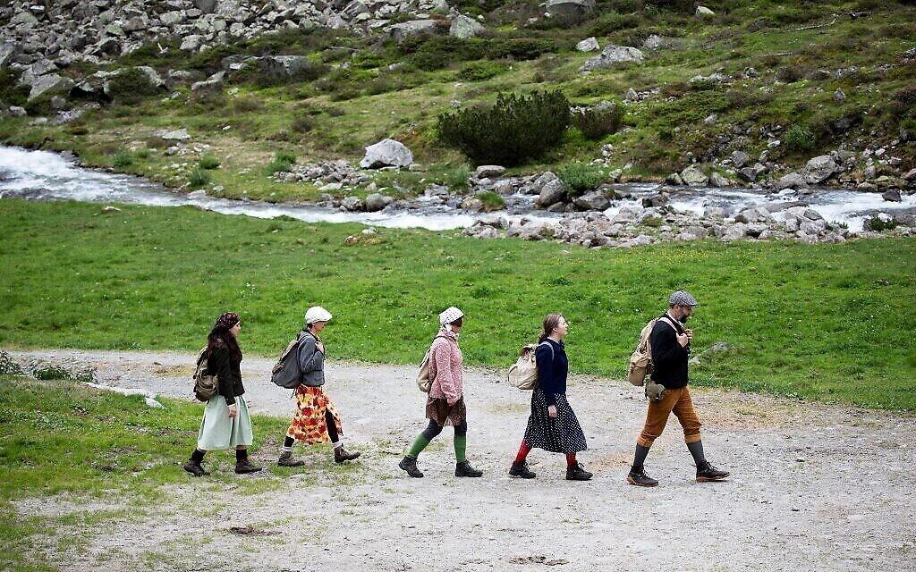 Des spectateurs suivent la troupe de théâtre Teatro Caprile à l'alpage Windbach dans les Alpes de Krimmler Tauern, à la frontière entre l'Autriche et l'Italie, en direction du col de Krimmler, près de Krimml, le 25 juin 2021.(ALEX HALADA/AFP)