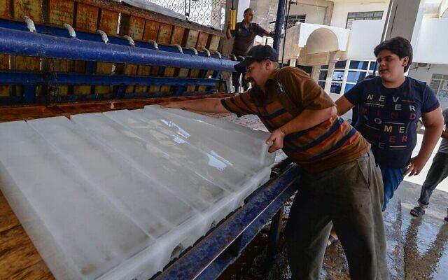 Un Irakien achète un bloc de glace dans une usine de Mossoul, dans le nord du pays, le 3 juillet 2021. (Crédit :  Zaid Al-Obeidi/AFP)