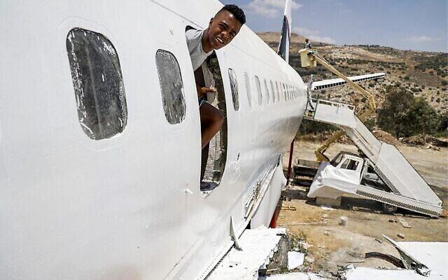 Un jeune jette un coup d'œil par une ouverture dans le fuselage d'un Boeing 707 transformé en restaurant par les frères jumeaux palestiniens Atallah et Khamis al-Sairafi, près de la ville de Naplouse en Cisjordanie, le 5 juillet 2021. (Crédit : JAAFAR ASHTIYEH / AFP)