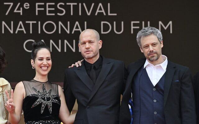 """(De gauche à droite) L'actrice israélienne Nur Fibak, le réalisateur israélien Nadav Lapid et l'acteur israélien Avshalom Pollak posent à leur arrivée à la projection du film """"Ha'Berech"""" (Le genou d'Ahed) lors de la 74e édition du Festival de Cannes, à Cannes, dans le sud de la France, le 7 juillet 2021. (Crédit : John MACDOUGALL / AFP)"""