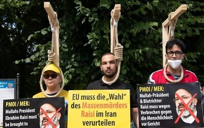 Des manifestants posent avec des potences factices alors qu'ils participent à une manifestation appelée par le Conseil national de la résistance iranienne (CNRI) contre le régime iranien, devant la porte de Brandebourg à Berlin, le 10 juillet 2021. (Crédit : Paul Zinken/AFP)