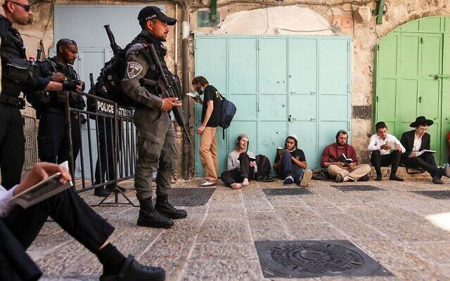 Des hommes juifs à l'extérieur de l'enceinte de la mosquée Al-Aqsa à Jérusalem, alors que les forces de sécurité israéliennes montent la garde lors du jeûne annuel de Tisha BeAv (9 du mois d'Av), le 18 juillet 2021. (Crédit : AHMAD GHARABLI / AFP)